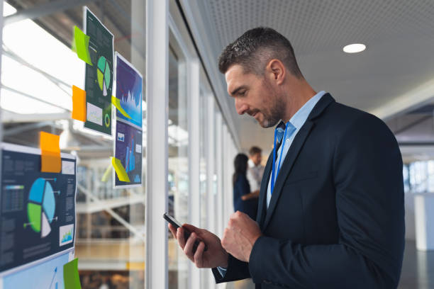 Businessman using mobile phone near glass wall in office stock photo