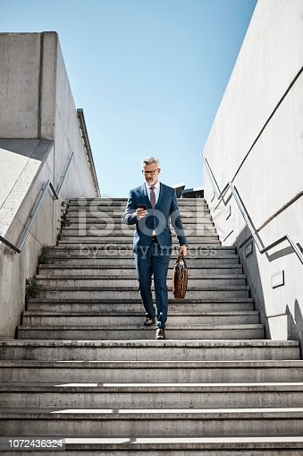 Full length of businessman using mobile phone on steps. Confident professional is moving down staircase against clear sky. Mature executive is wearing suit in city.