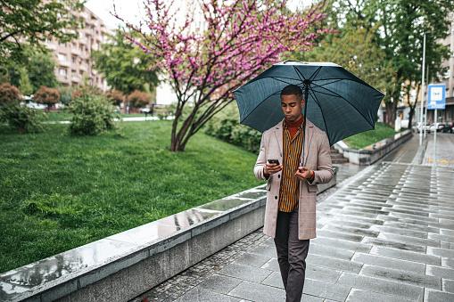 Businessman walking with umbrella