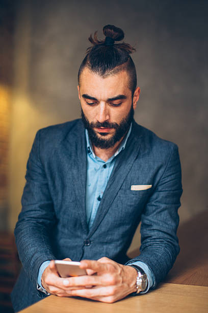 Businessman using mobile phone Young businessman using mobile phone man bun stock pictures, royalty-free photos & images