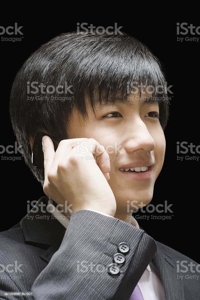 Businessman using mobile phone, smiling, close-up foto de stock libre de derechos