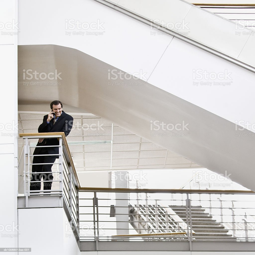 Businessman using mobile phone, smiling foto de stock libre de derechos