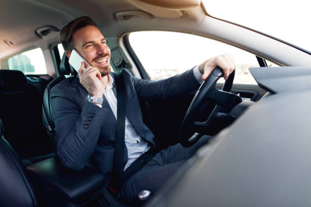 Businessman using mobile phone while driving a car stock photo