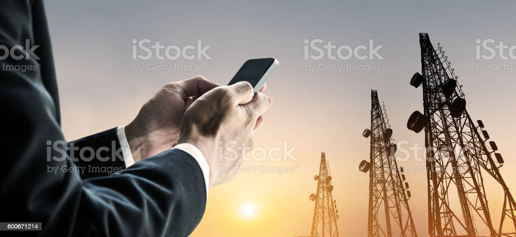Businessman using mobile phone with multi exposure Telecommunication towers stock photo