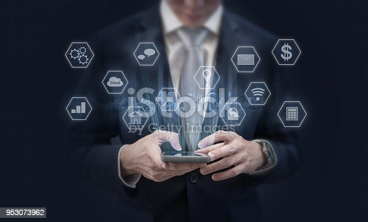 istock Businessman using mobile smart phone and application icons. Mobile application, social media and e-commerce technology 953073962