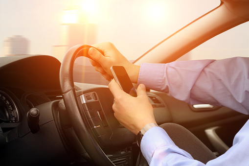 istock Businessman using mobile smart phone while driving the car. 837009352