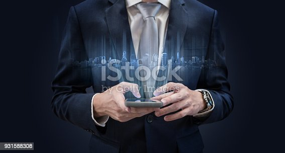 1082409706 istock photo Businessman using mobile smart phone, with futuristic buildings hologram 931588308