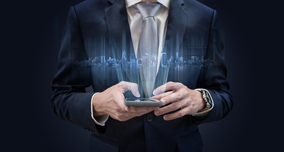 istock Businessman using mobile smart phone, with futuristic buildings hologram 931588308