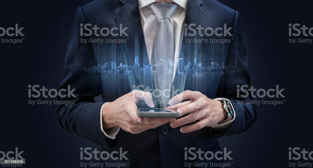 Businessman using mobile smart phone, with futuristic buildings hologram stock photo