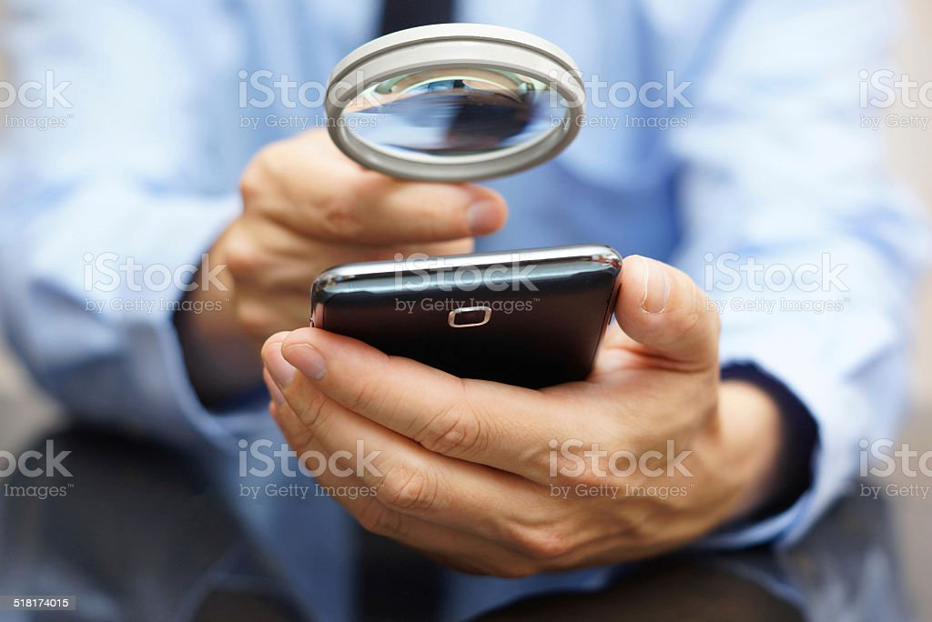 Businessman using mobile smart phone with magnifying glass - Royalty-free Adult Stock Photo