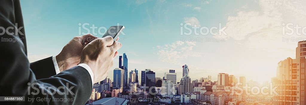 Businessman using mobilephone with panoramic cityscape in sunrise, vintage tone stock photo