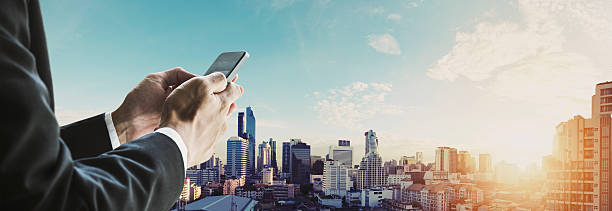Businessman using mobilephone with panoramic cityscape in sunrise, vintage tone - Photo
