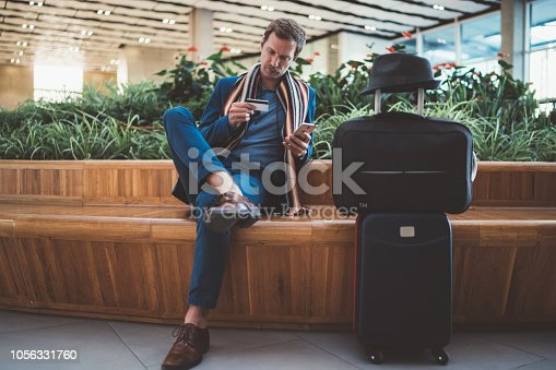 Businessman in casual business clothing using smartphone and credit card for online payments