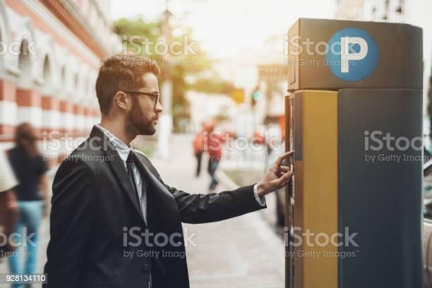 Businessman using parking meter outdoors picture id928134110?b=1&k=6&m=928134110&s=612x612&h=ijziewhbzo8zmg1lae hy4widamet94yik0b1hmkagg=
