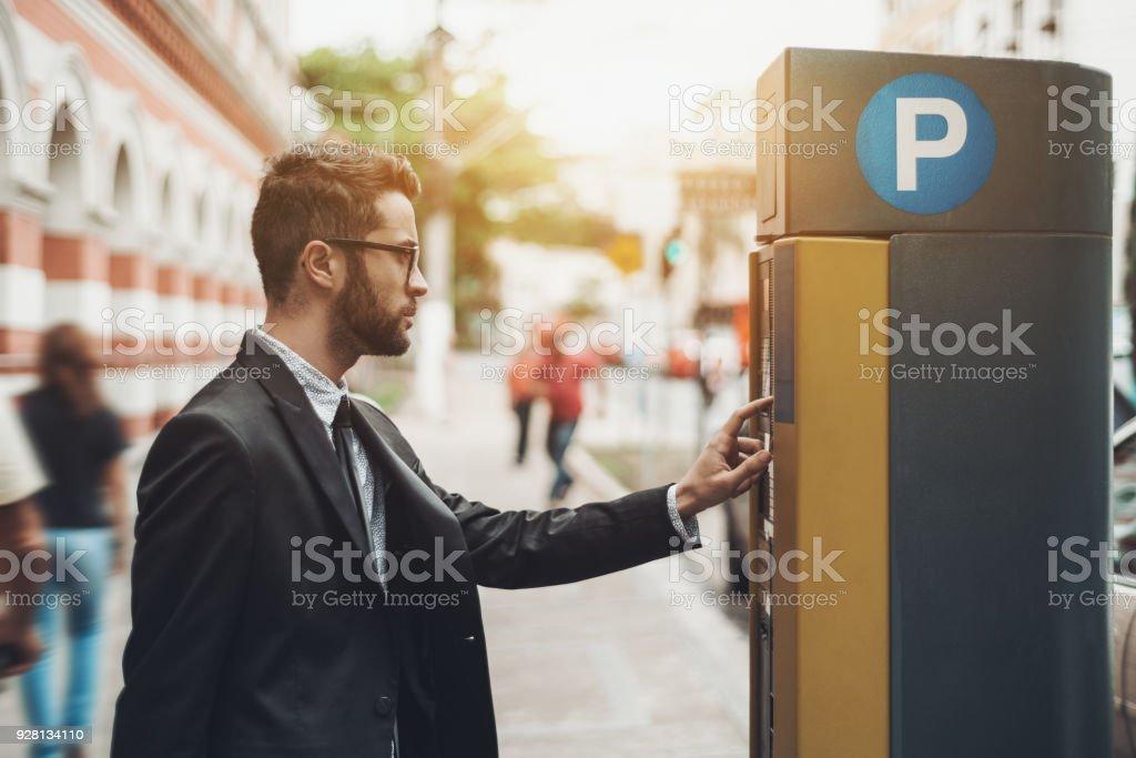 Businessman using Parking Meter outdoors stock photo