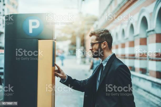 Businessman using parking meter outdoors picture id937868170?b=1&k=6&m=937868170&s=612x612&h=njdh  9wuiddybyw6g 7ryza4i 9ofpm4se3spt paw=