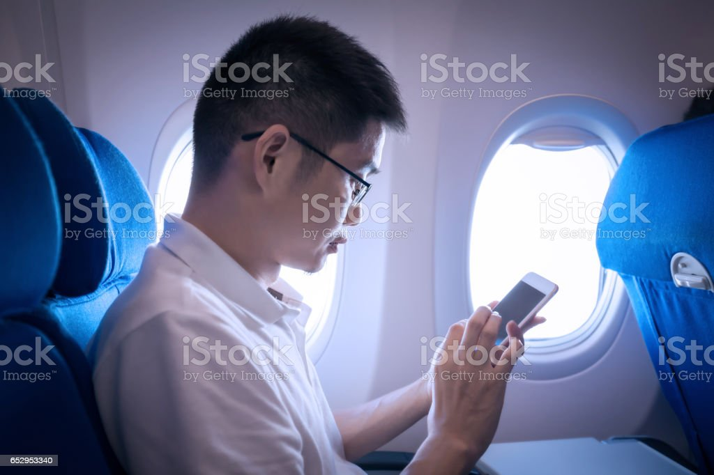 Businessman using phone in airplane travelling stock photo