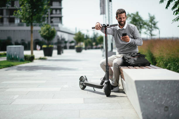 Businessman using phone while on electric scooter stock photo