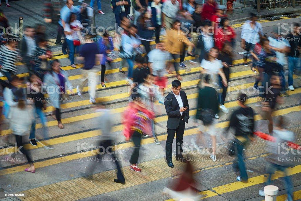 Geschäftsmann mit Smartphone in Menge – Foto