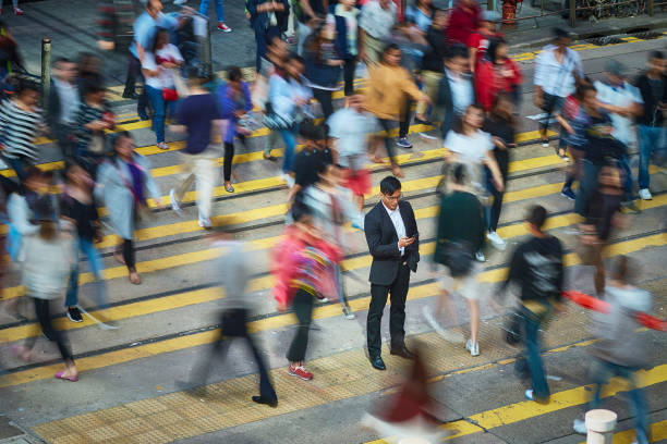 businessman using smart phone amidst crowd - crowded stock pictures, royalty-free photos & images
