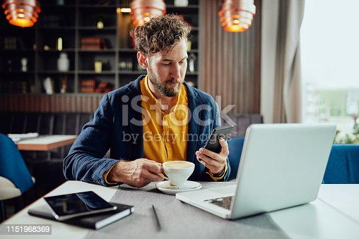 Young serious Caucasian bearded businessman dressed smart casual using smart phone and drinking coffee. Cafe interior.