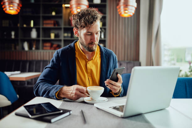 Businessman using smart phone and drinking coffee in cafe. Young serious Caucasian bearded businessman dressed smart casual using smart phone and drinking coffee. Cafe interior. cafe stock pictures, royalty-free photos & images