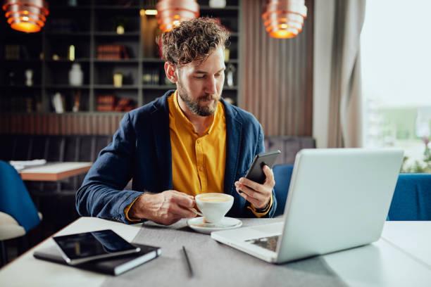 Geschäftsmann mit Smartphone und Kaffee im Café. – Foto