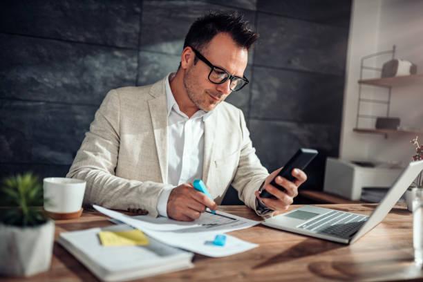 Geschäftsmann mit Smartphone und Text in seinem Büro – Foto