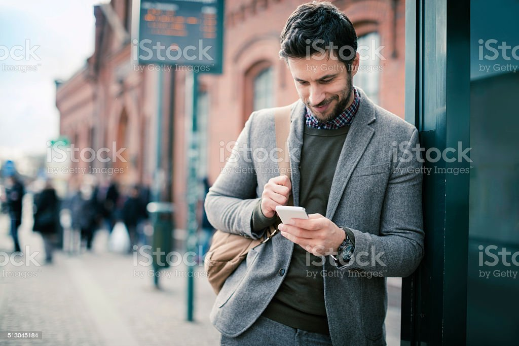 Businessman using smart phone at bus station stock photo