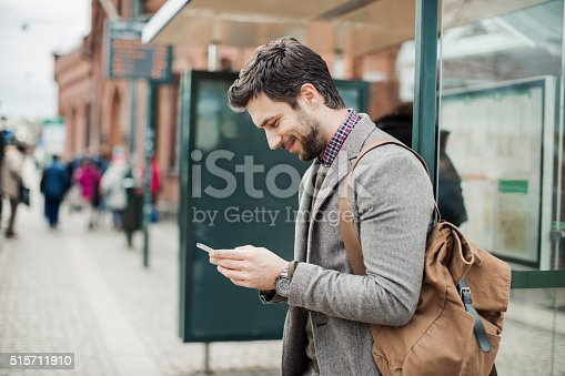 istock Businessman using smart phone at bus station 515711910