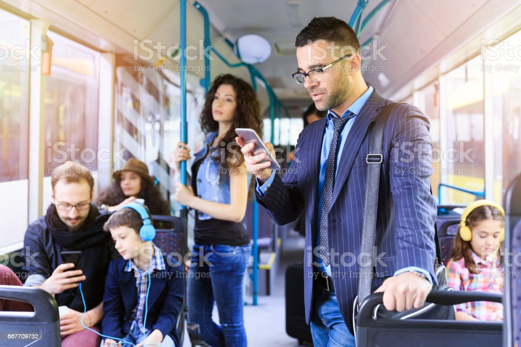 Businessman using smart phone in a bus stock photo