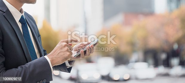 istock Businessman using smart phone in shopping street in city background and copy space.Concept of people using taxi apps online technology. 1009929212