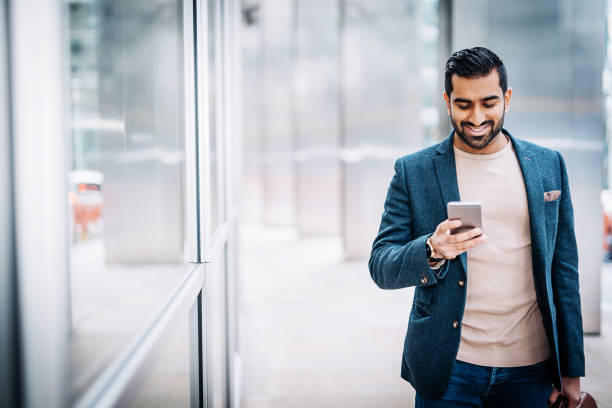 Businessman using smart phone near office building Businessman in London traveling in smart casal clothing and going for a meeting yeah right stock pictures, royalty-free photos & images