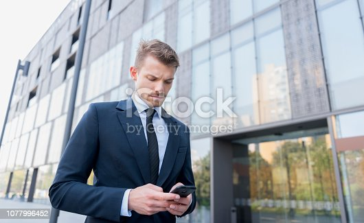 Businessman using smart phone at outdoors.