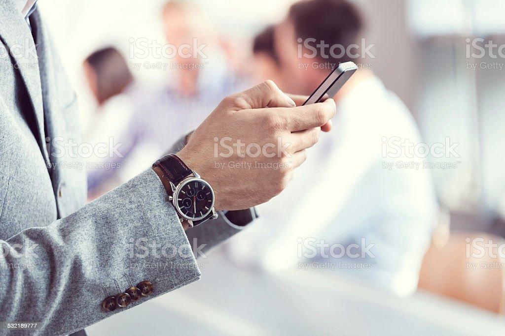 Businessman using smart phone Businessman texting on smart phone during business meeting. Close up of hands. 2015 Stock Photo