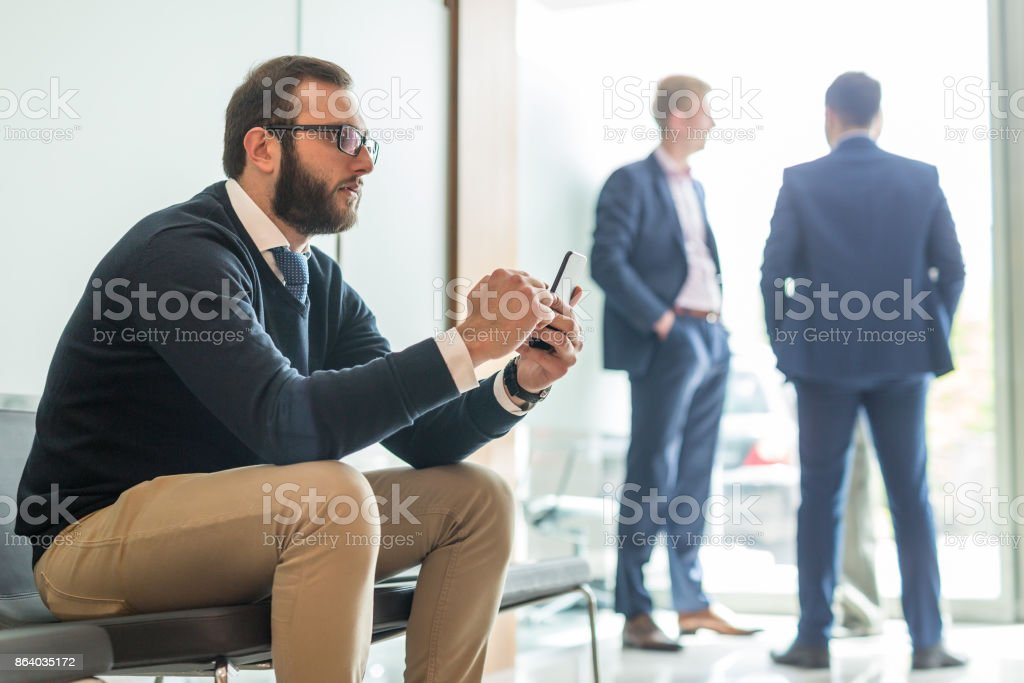 Businessman using smart phone while sitting in waiting room. stock photo