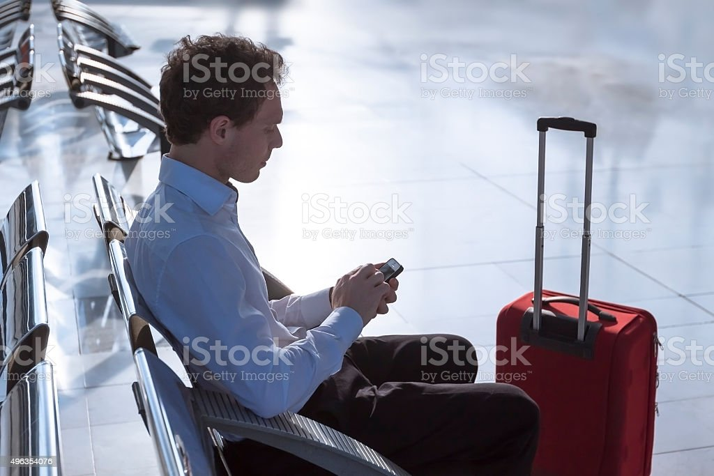 Businessman using smartphone at airport stock photo