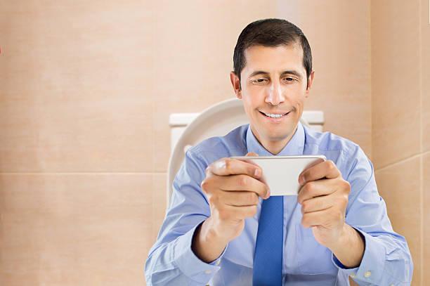 businessman using smartphone at the bathroom - cell phone toilet stockfoto's en -beelden