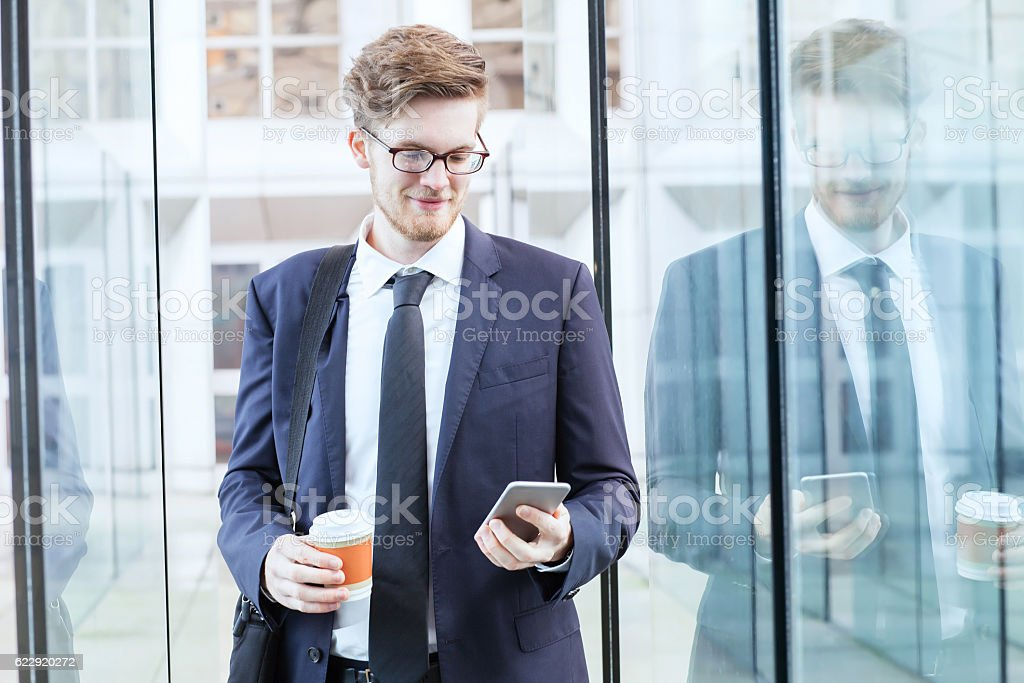 businessman using smartphone in airport stock photo