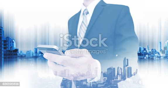 635942136istockphoto Businessman using smartphone, with double exposure city, business communication technology 636595836