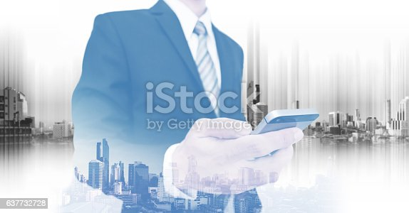 635942136istockphoto Businessman using smartphone, with double exposure city, business communication technology 637732728