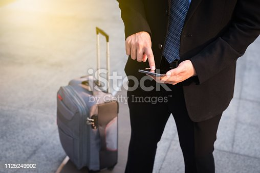 istock Businessman using smartphone with suitcase. 1125249902