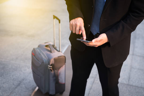 businessman using smartphone with suitcase. - business travel stock pictures, royalty-free photos & images