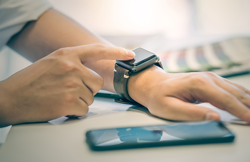Businessman using smartwatch while working at office, man touching on smartwatch screen.New technology concept