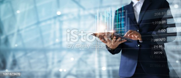 1127866562 istock photo Businessman using tablet analyzing sales data and economic growth graph chart.  Business strategy.  Digital marketing. 1051623470