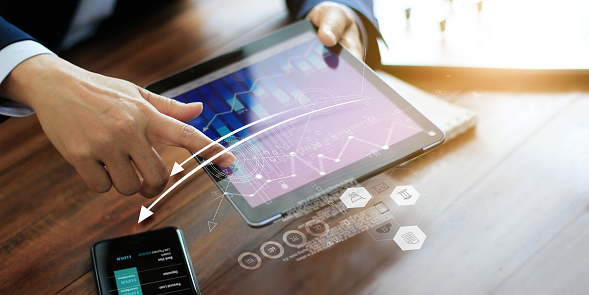1025744818 istock photo Businessman using tablet analyzing sales data and economic growth graph. Business planning and strategy. Digital marketing. 1182777181