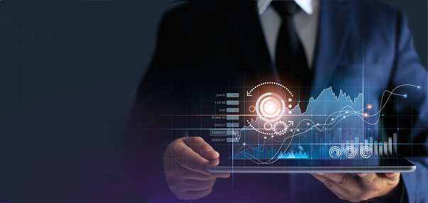 Businessman using tablet analyzing sales data and economic growth graph chart. Business strategy. Abstract icon. Stock market, Banking and Digital marketing.