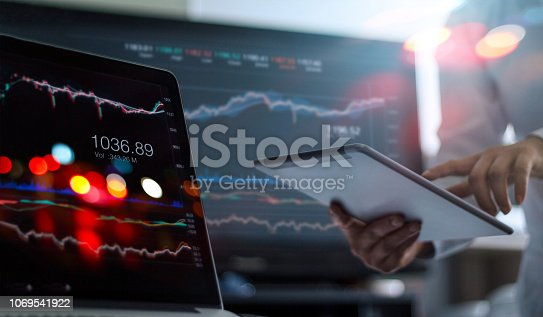istock Businessman using tablet and laptop for analyzing data stock market in monitoring room background, forex trading graph, stock exchange trading online, financial investment concept. All on laptop screen are designed up. 1069541922