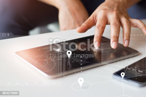istock Businessman using tablet and smartphone with global network worldwide connection technology on virtual screen 654078992