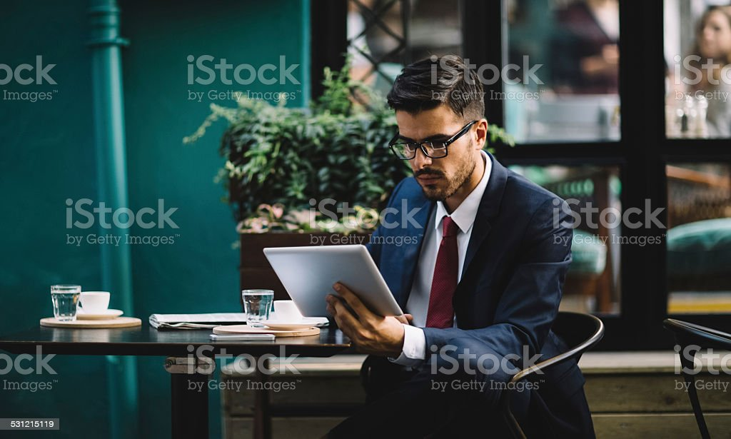 Businessman using tablet at cafe stock photo
